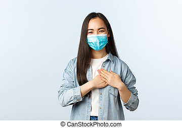 Social distancing lifestyle, covid-19 pandemic everyday life and leisure concept. Delighted happy asian girl being praised, feeling touched and thankful, touching heart, smiling in medical mask