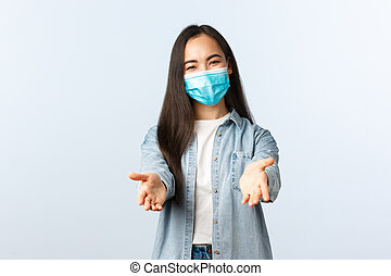 Social distancing lifestyle, covid-19 pandemic everyday life and leisure concept. Friendly lovely asian woman in medical mask reaching hands forward to take something or hold, white background