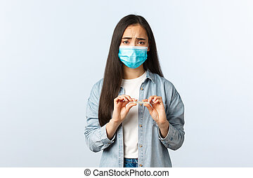 Social distancing lifestyle, covid-19 pandemic everyday life and leisure concept. Sick asian girl test positive coronavirus, measure temperature, holding thermometer, wear medical mask, have fever