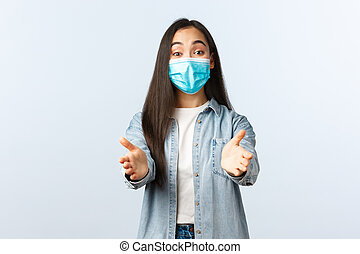 Social distancing lifestyle, covid-19 pandemic everyday life and leisure concept. Smiling asian woman in medical mask reaching hands forward to take or hold something adorable