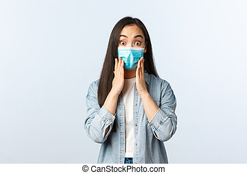 Social distancing lifestyle, covid-19 pandemic everyday life and leisure concept. Surprised astonished asian girl looking impressed, wear medical mask, react to wonderful news, say wow