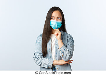 Social distancing lifestyle, covid-19 pandemic everyday life and leisure concept. Thoughtful concerned asian girl thinking of plan, wear medical mask, pondering serious face, looking up