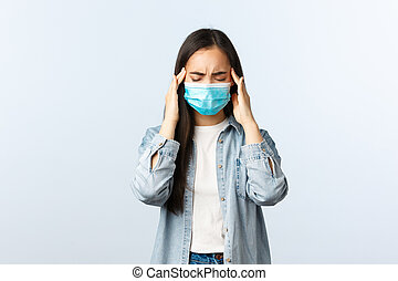 Social distancing lifestyle, covid-19 pandemic everyday life and leisure concept. Troubled asian girl got positive coronavirus test, feeling sick, wear medical mask, have headache or migraine