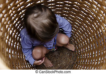 Scared child hides in a laundry basket.