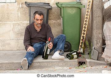 sad drunk man sitting on sidewalk near trashcan
