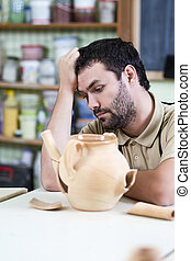 Social Issues.Sad and Down Caucasian Male Ceramist In Front...