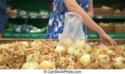 Social market concept, cheap products. woman picks onions on the counter in the store in a plastic bag