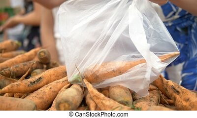 Social market concept, cheap products. woman picks up dirty carrots on the counter in the store in a plastic bag