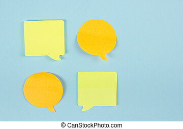 Social Media Chat Concept. Yellow blank empty chat bubble for text on blue background. Symbol of live chat. Office table desk with set of colorful supplies. Top view and copy space for ad text