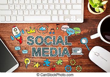Social Media concept with workstation on a wooden desk