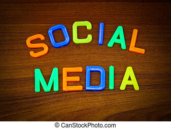 Social media in colorful toy letters on wood background