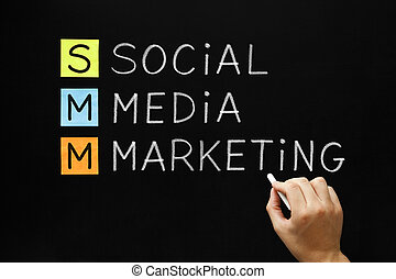 Hand writing Social Media Marketing with white chalk on blackboard.