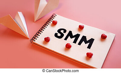 Social media marketing concept. The inscription SMM on a pink background