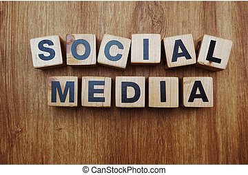 Social Media word created with cubes alphabet letters on wooden background