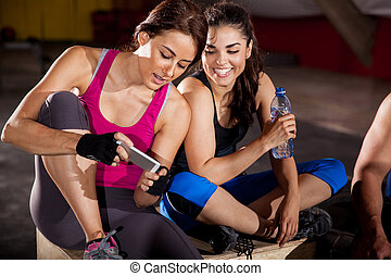 Social networking at a gym - Cute female friends texting and...
