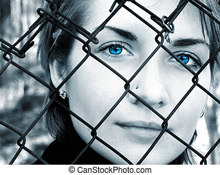 B&W picture of crying girl behind metal fence