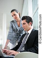 socios de negocio, en, vestíbulo, con, computador portatil
