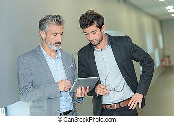 socios de negocio, trabajando, en, pasillo, con, electrónico, tableta