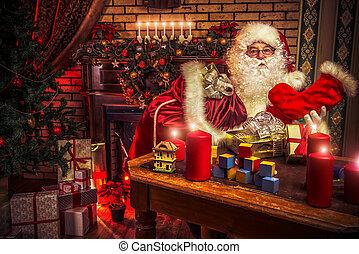 sock for gifts - Santa Claus making Christmas gifts at home.