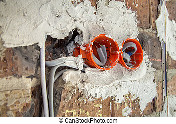 Socket orange boxes with wires in a wall. Cabling installation of electrical wires sticking out from electrical sockets hole on brick wall.