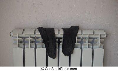 Socks, drying on heating radiator after washing. - Socks,...
