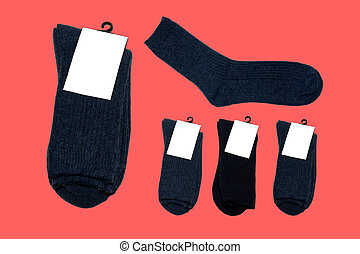 Socks made of natural wool. Warm socks. Collection of colorful socks. Socks with label. On red background. Isolated.