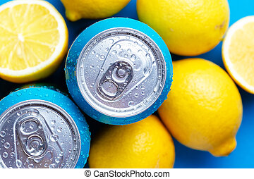 Soda cans and lemons over blue background