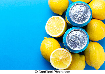 Soda cans with condensation drops and lemons over blue background