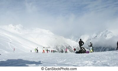 Skiers go down from mountain against clouds and blue sky -...