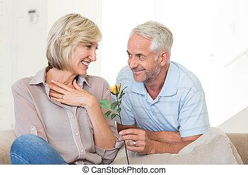 sofá, sorrindo, dar, mulher homem, flor, sentando