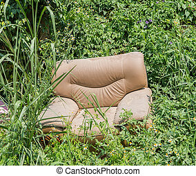 sofa abandoned in the grass