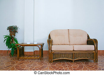 sofa and rattan table in an interior against wall