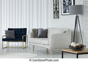 Sofa by white brick wall