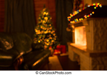 Sofa, fireplace and decorated Christmas tree defocused background