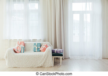 sofa in the interior of a white room with colorful gifts and flowers