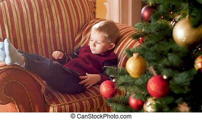 sofa, métrage, noël, quoique, utilisation, amusement, brouter, enfant garçon, suivant, arbre., internet, 4k, avoir, peu, tablette, mensonge, fetes, celebrations., hiver, informatique
