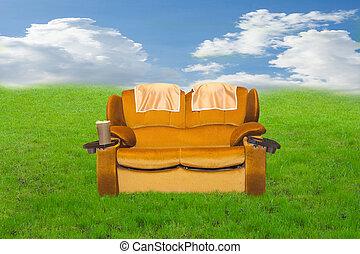 sofa on a green field