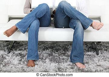 sofa, paar, beine kreuzten, sitzen