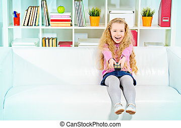 sofa sit - Cute joyful girl sitting on a sofa at home with a...