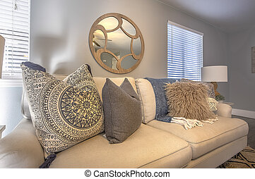 Sofa with fluffy pillows inside a living room with round mirror and gray wall