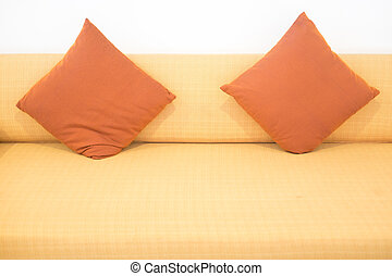 Sofa with orange pillows in room