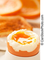 Soft boiled egg with toasted bread and slices of oranges in...
