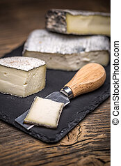 Soft cheese pieces on black slate