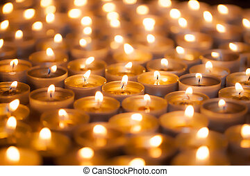 Soft dreamy image of bright candlelight from burning tea light candles. Christmas background image.