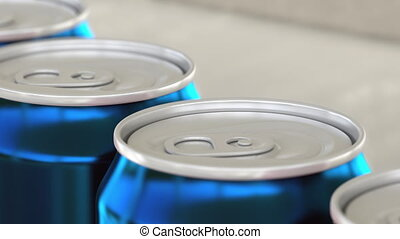 Soft drink or beer production line. Blue aluminum cans on...