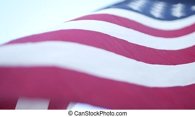 Soft focus close up of American Old Glory flag waving on wind. Stars and Stripes democracy, patriotism, freedom and Independence Day symbol. Star-spangled Banner, national pride and icon of liberty