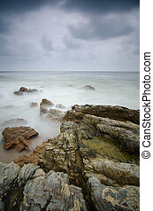 soft focus due to long exposure, image of rock at the shore with soft wave and dark cloud before raining