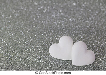 2 heart shaped candy pills on silver glittery background