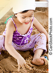 Asian little girl playing on sand