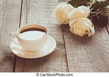 Soft full blown white roses with cup of black coffee on ...